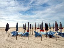 Colorful beach chairs and umbrellas on the beach front Stock Images