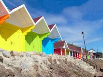 Colorful beach chalets by seaside stock photography