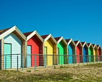 Colorful beach huts. Row of colorful beach bathing huts or chalets with blue sky background Royalty Free Stock Photo