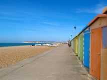 Colorful beach huts on pebble peach Seaford, East Sussex, England. Colorful beach huts on pebble peach in Seaford, East Sussex, England beneath a blue sky Royalty Free Stock Photos