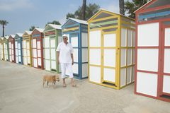 Colorful beach huts and senior man with dog Royalty Free Stock Images