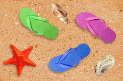 Colorful beach shoes and starfish over sand background Royalty Free Stock Images