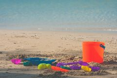 Colorful beach toys or children toys on sand beach with seascape view in the background. Selective focus Stock Image