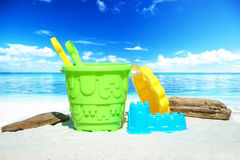 Colorful beach toys and driftwood Stock Photos
