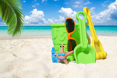 Colorful beach toys under palm frond Stock Photo