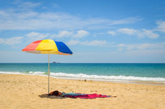 Colorful beach umbrella on the sandy beach on summer day. Naitho Royalty Free Stock Photo