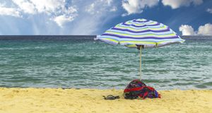Colorful beach umbrella. Towels and sandals under colorful beach umbrella inside green ocean on summer day Royalty Free Stock Images