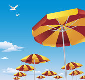Colorful beach umbrellas against blue sky. Several rows of brightly colored red and yellow beach umbrellas against brilliant blue sky with white clouds. Two Stock Images