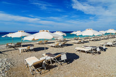Colorful beach umbrellas with deck chairs pebble beach and island in the distance royalty free stock images
