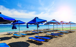 Colorful beach umbrellas with deck chairs pebble beach and island in the distance royalty free stock photos