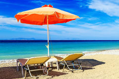 Colorful beach umbrellas with deck chairs pebble beach and island in the distance royalty free stock photography