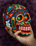 Colorful Beaded Skull on Hand. Colorful Beaded Skull from mexican traditional huichol bead art, symbol of the day of the dead, isolated on black Stock Photo