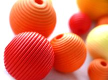 Colorful beads. Red. orange and yellow wooden beads on white royalty free stock photo