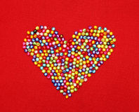 Colorful beads heart shape isolated on red Royalty Free Stock Image
