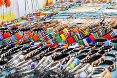 Colorful beads and leather handmade bracelets, bangles and necklaces at local craft market in South Africa. Traditional african souvenirs. Ethnic tribal design stock image
