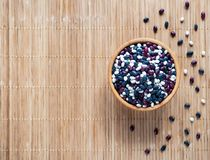 Colorful beans in a wooden bowl on a bamboo napkin stock photos