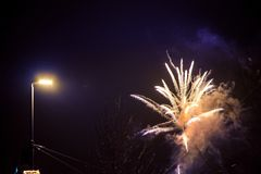 New Year celebration. Colorful, beautiful fireworks on the night sky over the city. New Year celebration. Blurry, falling stars stock photos