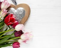 Colorful beautiful tulips and big wooden heart on the white wooden table. Valentines, spring background. floral mock up royalty free stock photos