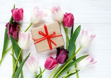 Colorful beautiful tulips and gift box on the white wooden table. Valentines, spring background. floral mock up with copyspace royalty free stock photo