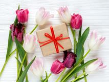 Colorful beautiful tulips, gift box on white wooden table. Valentines, spring background. stock photography
