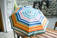 Colorful beautiful umbrella wet rain on table while raining Stock Photography
