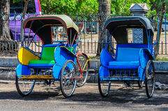 Colorful becak, typical local transport in Solo, Indonesia. Woman in the textile market in Solo on Java Island, Indonesia Stock Photos