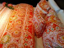 Colorful bedclothing. With abstract print in orange colours and roses Stock Photo