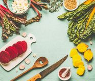 Colorful beetroot cooking preparation. Red and yellow sliced beetroot, chard leaves and ingredients on light blue kitchen table. Background, top view, frame Royalty Free Stock Image
