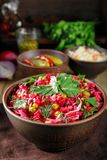 Colorful beetroot salad vinaigrette in a clay bowl. Vinaigrette salad with boiled vegetables, pickled cucumbers, sauerkraut and canned green peas in a clay bowl royalty free stock photo