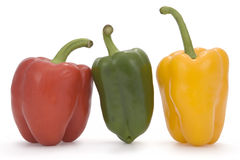 Colorful bell peppers. Side view of ripe red, green and yellow bell peppers isolated on white background Royalty Free Stock Image