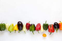 Colorful bell peppers and eggplants on white background. Stock Photo