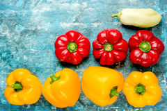 Colorful bell peppers, fresh sweet peppers on blue background Royalty Free Stock Photos