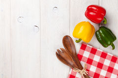 Colorful bell peppers and kitchen utensil Royalty Free Stock Photography