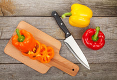 Colorful bell peppers and kitchen utensils Royalty Free Stock Photos