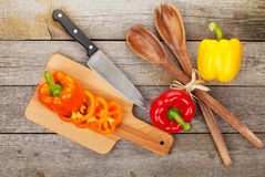 Colorful bell peppers and kitchen utensils Royalty Free Stock Photo