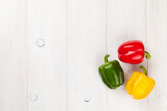 Colorful bell peppers on white wooden table Stock Photo