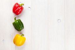 Colorful bell peppers on white wooden table Royalty Free Stock Images