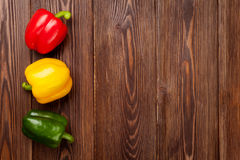 Colorful bell peppers on wooden table Royalty Free Stock Photos