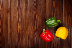 Colorful bell peppers on wooden table Stock Photos
