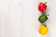Colorful bell peppers on wooden table Stock Images