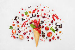 Colorful berries in waffle cone on light background from above. Dietary and healthy dessert. Flat lay styling. Royalty Free Stock Photos