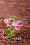 Colorful berry smoothies on a wooden background. Healthy cold milkshake with blueberries, mint, raspberries. Copy space. A pair of margarita glasses full of Royalty Free Stock Photography