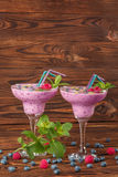 Colorful berry smoothies on a wooden background. Healthy cold milkshake with blueberries, mint, raspberries. Copy space. A pair of margarita glasses full of Stock Image