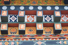 Colorful Bhutanese architecture. A woodwork on the window on Bhutanese house with traditional decorations. In Bhutan the windows and doors are designed with Royalty Free Stock Images
