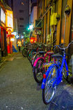 Colorful bicycles in a row at outdoors of the beautiful famous Kabukicho red lights district, surrounding of big. Buildings and advertisements, located in Tokyo stock photos
