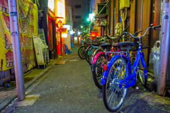 Colorful bicycles in a row at outdoors of the beautiful famous Kabukicho red lights district, surrounding of big. Buildings and advertisements, located in Tokyo royalty free stock photos