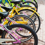 Colorful bicycles stand on a parking lot for rent Stock Photos