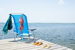 Flip-flops, bikini and swimming trunks on a pier. A colorful bikini and a pair of blue swimming trunks drying on a blue deck chair, and two pair of flip-flops on stock photography