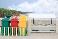 Colorful bin and signage on blue sky background. Multi-colored bins for separating waste with blue sky background Royalty Free Stock Images