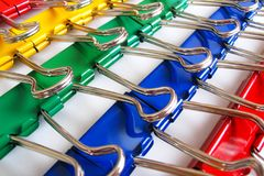 Colorful binder clips. Red, yellow, green, and blue binder clips in rows Royalty Free Stock Images